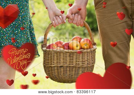 Basket of apples being carried by a young couple against happy valentines day