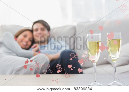 Couple resting on a couch with flutes of champagne against valentines heart design