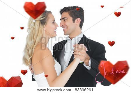 Sweet married couple dancing viennese waltz against valentines love hearts