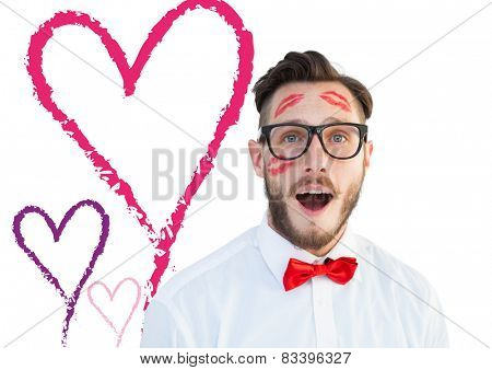 Geeky hipster with kisses on his face against valentines love hearts