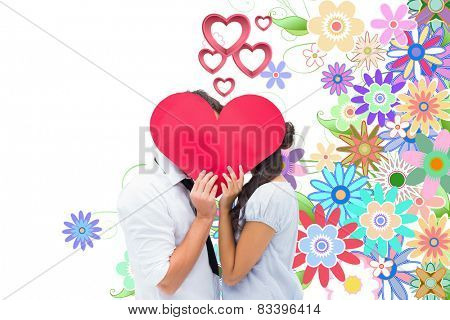 Couple covering their kiss with a heart against digitally generated girly floral design