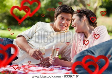 Man smiling as he looks at his friend during a picnic against hearts