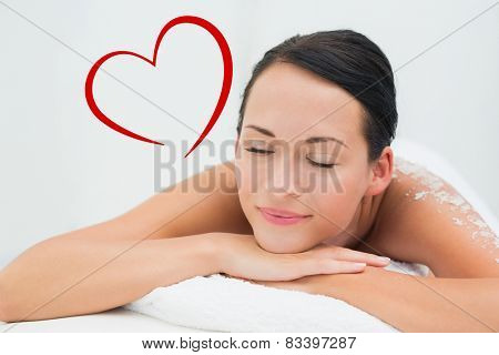Peaceful brunette lying with salt scrub on back against heart