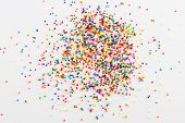 foto of sprinkling  - Colorful sprinkles spilled from a jar on white table - JPG