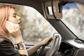 pic of dangerous  - Concept of danger driving. Young woman driver redhaired girl talking on mobile phone smartphone while driving the car.