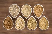 stock photo of whole-grain  - An assortment of whole grains in bowls over a wooden background - JPG
