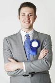 stock photo of rosettes  - Portrait Of Smiling Politician Wearing Blue Rosette - JPG
