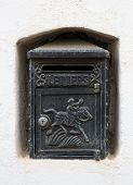picture of niche  - A black cast iron letterbox in a white wall niche with an engraving of a horse and knight and the word LETTERS - JPG