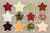 stock photo of olive shaped  - Selection of dips for snacks in star shaped dishes over bamboo background - JPG