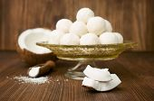 picture of coir  - candies in coconut flakes and fresh coconut on a wooden background - JPG