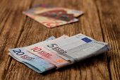 stock photo of plastic money  - Horizontal photo of three euro bills and two credit cards in background placed on old worn wooden board - JPG