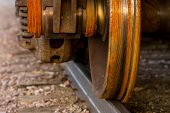 stock photo of train-wheel  - A detailed view of a rusty train wheel on a railroad track - JPG