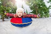 foto of inflatable slide  - Smiling girl on snow tube in winter during day in the fir tree forest - JPG