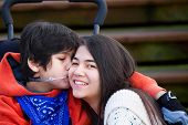 stock photo of little sister  - Disabled little boy kissing his big sister on cheek while seated in wheelchair - JPG