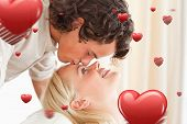 stock photo of fiance  - Close up of a man kissing his fiance on the forehead against love heart pattern - JPG