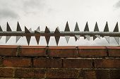 stock photo of spike  - Sharp rotating metal spikes protecting the top of a wall in East London - JPG