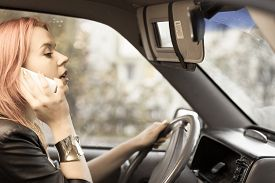 foto of dangerous  - Concept of danger driving. Young woman driver redhaired girl talking on mobile phone smartphone while driving the car. ** Note: Soft Focus at 100%, best at smaller sizes - JPG