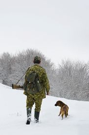 picture of hunter  - Male hunter in camouflage clothes walking on the snow field with hunting rifle during a hunt dog follows him foggy weather - JPG