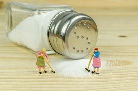 stock photo of crystal salt  - Miniature toy housewives figures cleaning up spilled salt on wooden table - JPG