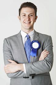 stock photo of politician  - Portrait Of Smiling Politician Wearing Blue Rosette - JPG