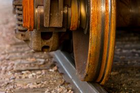 foto of train-wheel  - A detailed view of a rusty train wheel on a railroad track - JPG