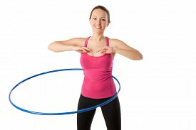 image of half-dressed  - fitness woman dressed in pink top and black leggins working with hula hoop smiling isolated over white - JPG