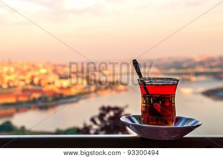 A gilded cup of tea or cay / tchai on the fence over the Golden Horn and Istanbul panorama