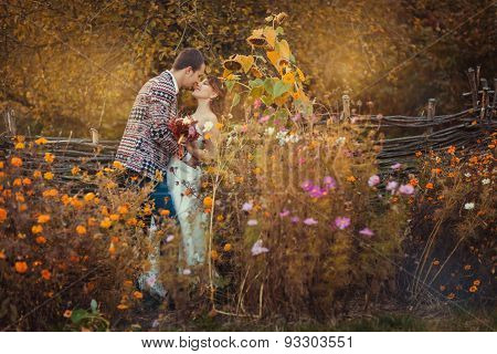 Newlyweds Are Embracing Among The Flowers