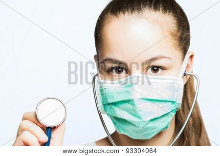 Girl in a doctors mask holding a stethoscope - medical concept