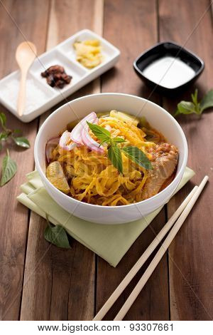 Curried Noodle Soup (khao Soi) With Coconut Milk On Wooden Table
