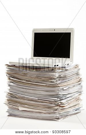 laptop computer over pile of documents