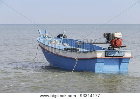 Small blue boat on the sea in afternoon