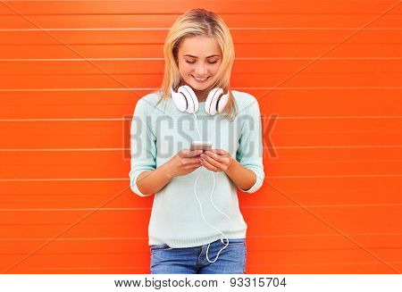 Fashion, Technology And People Concept - Pretty Smiling Girl Using Smartphone In Headphones Against