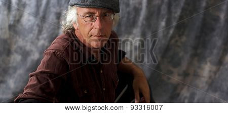 Blue Eyed Man With Glasses And Grey Hair Wearing Cap