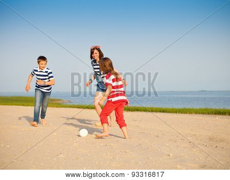 Brother And Sisters Play With A Beach Ball Outdoors