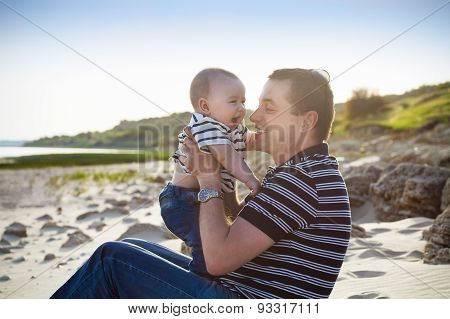 Young Father Playing With Baby Son As At The Beach