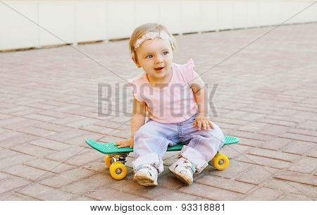 Portrait Of Cute Baby Sitting On The Skateboard Outdoors In City