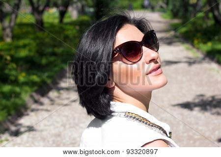 Summer mood. Portrait of a woman in sunglasses at the park