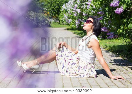 Summer mood. Woman with flowers. A woman is sitting on the pavement among the lilacs