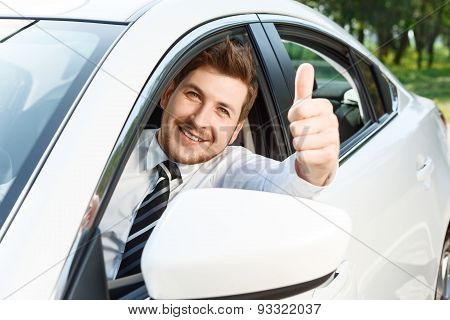 Young man doing thumbs up in car