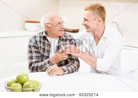 Grandson giving glass with water to his grandpa