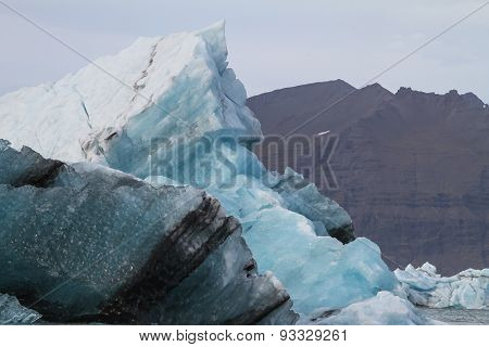 Blue Iceberg In Front Of Mountains At Jokulsarlon