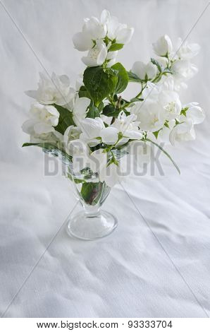 Beautiful Bouquet Of Jasmine In Glass Vase On White Background Crumpled Linen