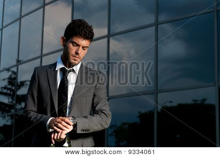 Young Businessman Looking Clock At Night On Modern Building Background