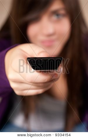 Young Woman With Remote Control Sitting On Sofa Close-up