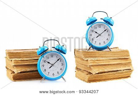 Blue alarm clock next to a books stack