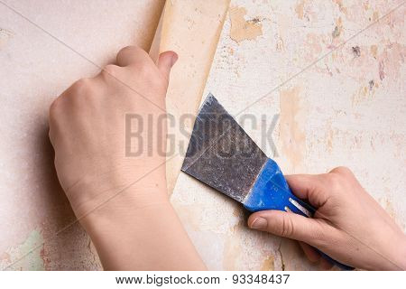 Hands Removing Wallpaper From Wall