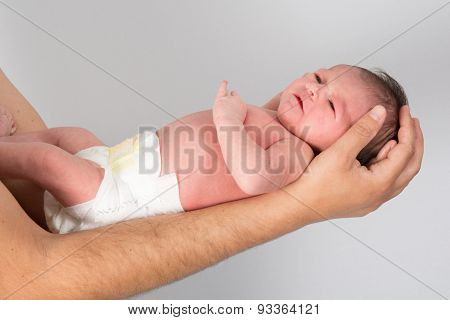 New Born Baby Is Held By His Father Isolated On Grey
