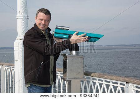 Confident  Man Standing Close To Ocean Tourist Watching Through Binoculars Or Telescope