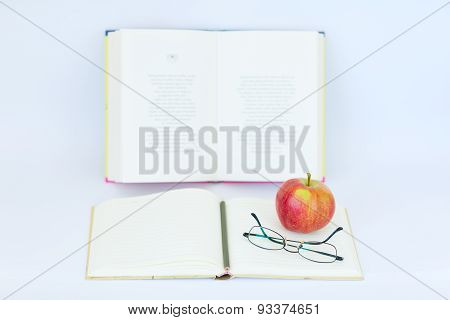 Open blank notebook with glasses, apple, and pencil on the top